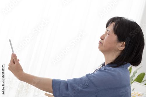 Fotografie, Obraz  携帯電話を離して見る女性、老眼、目を細める