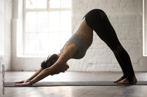 Young attractive woman practicing yoga, standing in Downward facing dog exercise Fototapeta