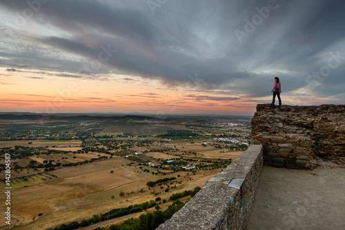 Photo Turista a contemplar o Pôr do Sol no castelo da vila mediaval de Monsaraz, Alent