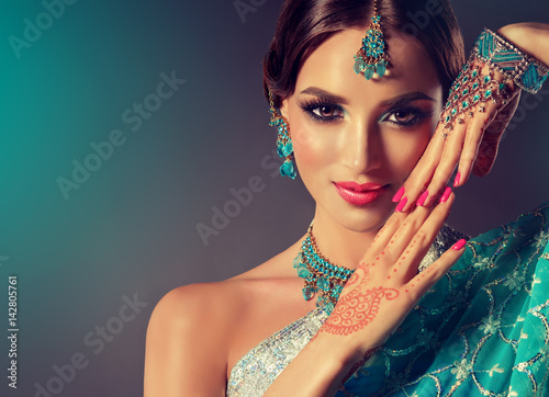Fototapeta Portrait  smiling of beautiful indian girl. Young indian woman model with blue kundan jewelry set . Traditional Indian costume  .  obraz