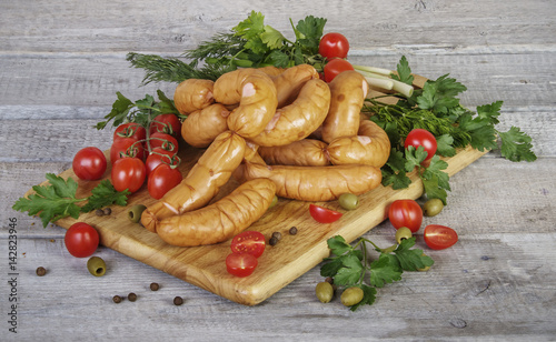 Fotografering  homemade sausages on wooden cutting board with parsley, dill, onion, tomatoes an