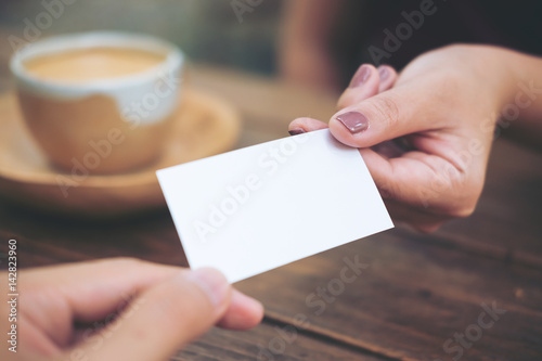 Valokuva  Business man giving  business card to business woman with coffee cup on wooden t