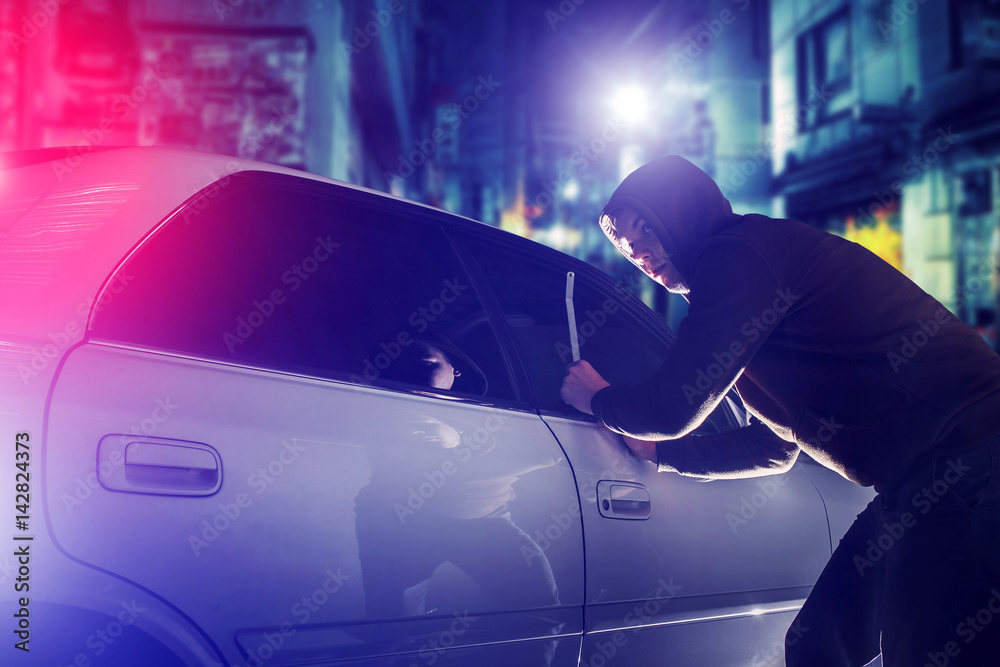 Fototapeta car thief in action at night. Car Security Theme.