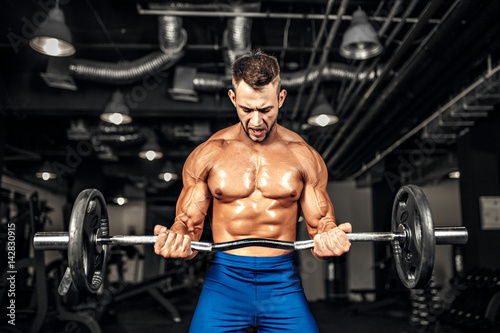 Poster Fitness Young handsome caucasian bodybuilder sportsman working out with a barbell in gym, doing biceps training.