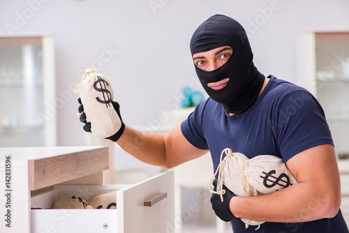 Robber wearing balaclava stealing valuable things Wallpaper Mural