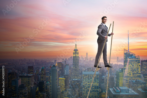 Businessman walking on stilts - standing out from the crowd Fototapet