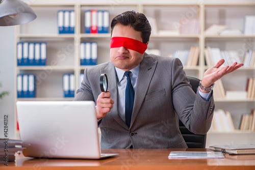 Blindfold businessman sitting at desk in office Wallpaper Mural