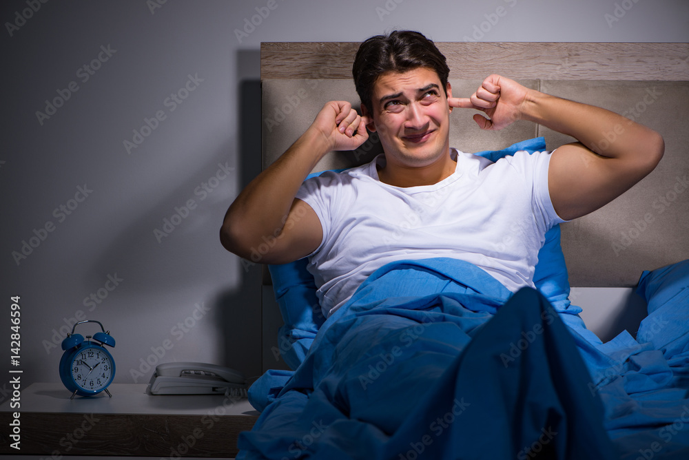 Fototapeta Young man struggling from noise in bed