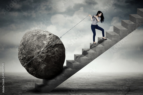 Obraz Female entrepreneur carrying big stone on the stair - fototapety do salonu