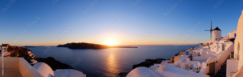 Fototapety, obrazy: Traditional apartments and windmills in Oia village on a sunset, panoramic image