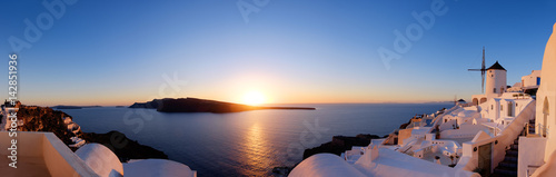 Poster Santorini Traditional apartments and windmills in Oia village on a sunset, panoramic image