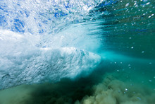 A Breaking Wave Forms A Vortex In Crystal Clear Ocean Water In This Underwater Image.