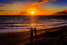 A Couple Watching The Sunset In Kauai