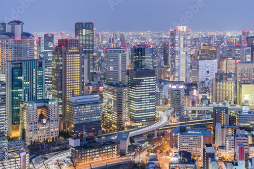 Naklejka premium Widok na miasto Osaka z drogą ekspresową i wysokim budynkiem o zmierzchu