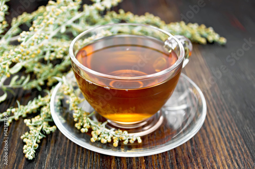 Tea with gray wormwood in glass cup on table Wallpaper Mural