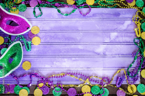 Photo Vibrant Mardi Graw background with masks, beads and coins and copy space