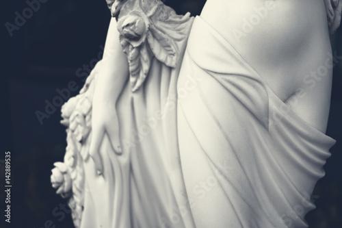Foto  White female figure sculpture in dark tone.