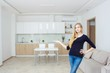 Real estate agent presenting modern house to client, woman Shows the kitchen.