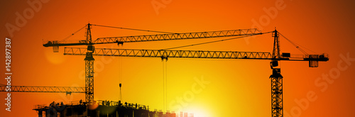 Fotografie, Obraz  Tower cranes and building silhouette with workers at sunrise.