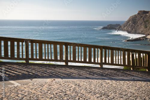 In de dag Inspirerende boodschap view on beautiful arrifana beach in blue sky by atlantic ocean with wooden fence, algarve, portugal