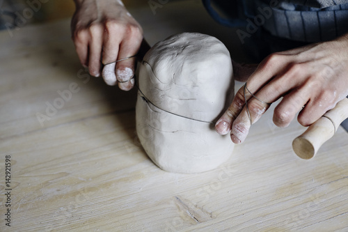 Leinwand Poster Woman hands close-up, forming crude clay in a potter's workshop studio