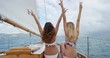 Beautiful girl friends enjoying view arms raised peace sign on sailboat in ocean on luxury lifestyle happy adventure travel vacation