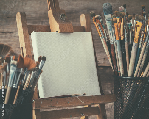 Photo  Artistic equipment: empty artist canvas on easel and paint brushes in a artist studio