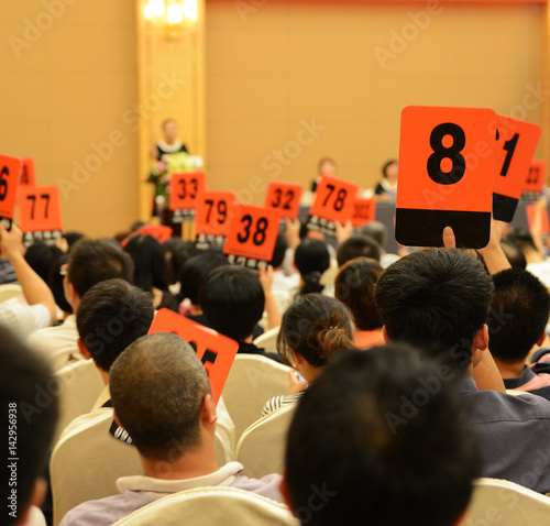 Photo People holding auction paddle to buy from auction.