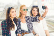 Three girls stand at the airport and looking at the tablet. A trip with friends.girls doing selfie