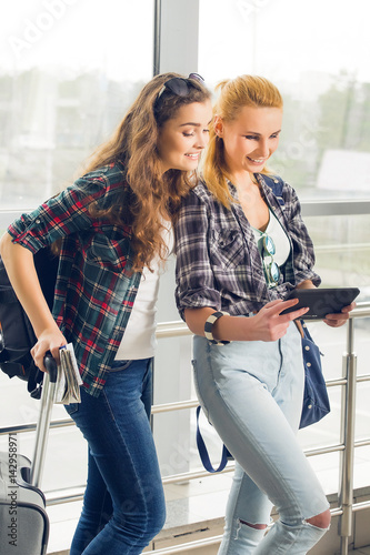 Two girls stand with suitcases at the airport and looking at