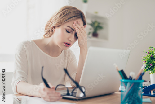 Overworked businesswoman suffering from headache and thinking how to end work Canvas-taulu