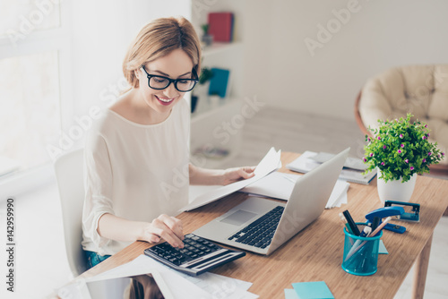 Photo Happy cute  pretty accountant working with computer and calculator