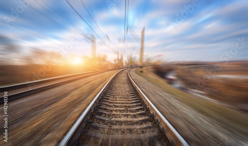 Deurstickers Spoorlijn Railroad in motion at sunset. Railway station with motion blur effect and colorful sky with clouds. Industrial concept background. Railroad travel, railway tourism. Blurred railway. Transportation