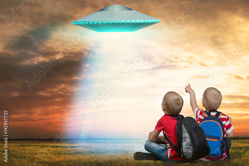 Foto op Canvas UFO Two younger brother looking at the unidentified flying object that appeared in the sky.