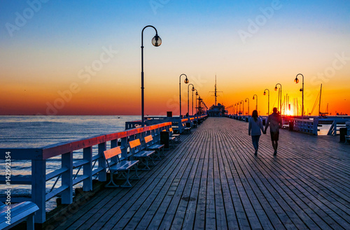 Fototapety, obrazy: Sunrise at the wooden pier (molo) in Sopot, Poland and an unrecognizable walking couple