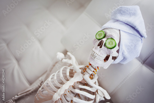 Skeleton in Spa salon with towel on her head and mask on her face, relaxes, care themselves Wallpaper Mural