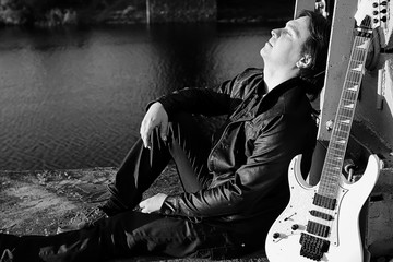 Monochrome man with an electric guitar in the industrial landsca