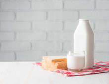 Fresh Milk And Bread Slice On Wooden Table Against White Brick Wall