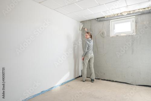 Foto Junge Frau streicht Kellerwände