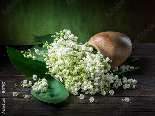 In de dag Lelietje van dalen Lily of the valley bouquet on the wooden table.