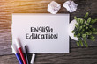 English Education word with Notepad and green plant on wooden background.