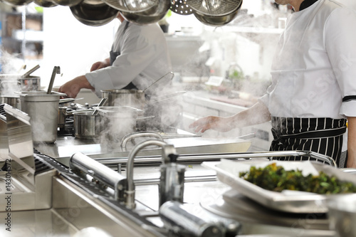 Foto op Canvas Restaurant Chef in hotel or restaurant kitchen cooking