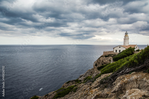 Garden Poster Lighthouse Amazing lighthouse Cala Ratjada is located in the easternmost part of Mallorca on the cliff. Lighthouse in cloudy day with beautiful view on the ocean. Balearic Island Mallorca, Spain.