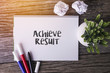 Achieve Result word with Notepad and green plant on wooden background.