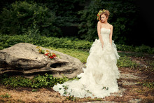 Fashionable Bride In A Lush White Dress Is Standing By A Large Stone In A Dark Nature.
