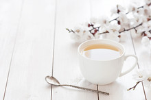 White Cup Of Hot Tea With Spring Flowers On A Light Wooden Background