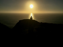 Silhouette Of Young Woman Sitting On Cliff As Sun Sets Behind Her