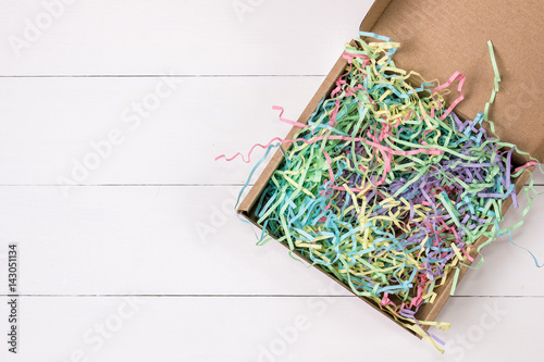 Fotografia, Obraz  Opened gift mailing kraft box with colorful crinkle tissue inside