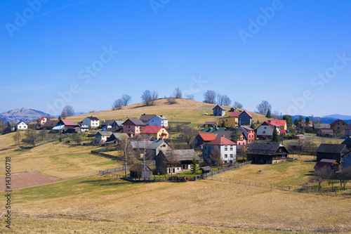 Fotomural  Traditional rural landscape and small village in the central Europe - houses, farms, fields, hills and meadows