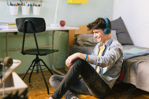 Teenage boy sitting on the floor in his room and listening music